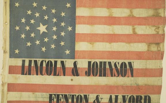 Campagnevlag voor Abraham Lincoln 1864 Deze vlag werd door het textielbedrijf Fenton & Alvord aangeboden aan president Abraham Lincoln, als campagnemateriaal voor zijn herverkiezingscampagne in 1864. Lincoln werd kort voor de verkiezingen vermoord en opgevolgd door vice-president Andrew Johnson. Het bedrijf bood dit campagnemateriaal uiteraard volledig belangeloos aan. Toen al, in 1864, was de Amerikaanse bedrijfswereld zo onbaatzuchtig.