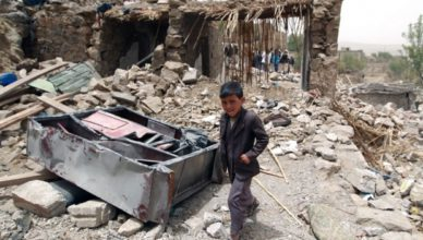 Een Jemenitisch jongetje loopt door de ruïnes van zijn dorp